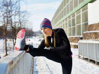 Junge Frau beim Stretching nach dem winterlichen Joggen durch den Schnee
