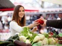 Attraktive Frau kauft auf einem Wochenmarkt Obst ein