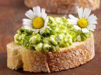 Brot mit grünem Hüttenkäse und Gänseblümchen
