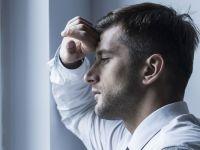 Mann mit weißem Hemd schaut erschöpft aus dem Fenster