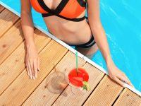 Frau mit flachem Bauch im Pool mit einem Drink