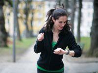 Dunkelhaarige Frau schaut beim Joggen auf ihre Uhr