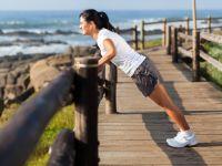 Frau macht am Strand positiven Liegestutz