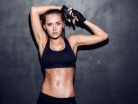 Sportliche junge Frau zeigt ihr Sixpack