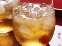 Ginger Ale mit Cocktailkirsche und Eiswürfeln