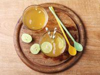 Zwei Gläser Ginger Ale mit Strohhalm und Limette auf einem runden Holzbrett