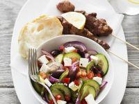 Griechische Fleischspießchen und buntem Salat mit Feta