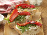Italienisches Weißbrot (Ciabatta) mit Ziegenkäse, Rauke und Paprika vom Grill