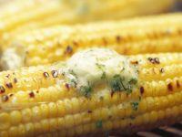 Maiskolben mit Kräuterbutter auf dem Grill