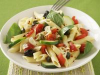 Pastasalat mit Oliven, Tomaten und Basilikumblättern