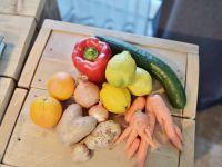 Verschiedene krumme Obst- und Gemüsesorten auf einer Holzkiste