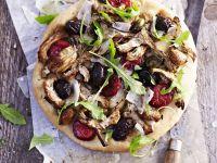 Pizza mit Artischocken, schwarzen Oliven, Rucola und scharfer Wurst (Chorizo)
