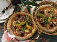 Pizza mit Tomaten, Sardellen, Schinken und Peperoni