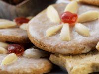 Plätzchen mit Zuckerguss und Mandeldekor