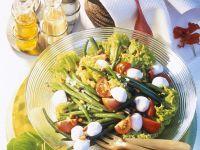 Salat mit grünen Bohnen, Mozzarella, Tomaten, Pinienkernen und Rosinen