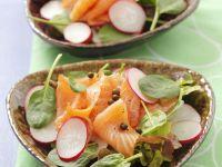 Salat mit Spinat, geräuchertem Lachs, Radieschen und Pfefferkörnern