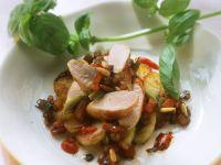 Salat von Bratkartoffeln, Kaninchen und Pinienkernen, dazu Basilikum