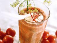 Scharfer Tomatendrink mit Kräutern und Joghurttupfer