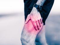 Mann hält sich sein schmerzendes Bein
