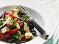 Schwarze Nudeln mit Mozzarella und Tomaten