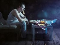 Verwahrloster Mann in Unterhemd sitzt mit Pizza und Chips vor dem Fernseher
