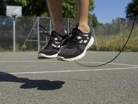 Bewegung pusht Stoffwechsel: Ein Springseil und Füße in der Luft auf einem Basketballplatz