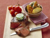 Steak mit Kräuterbutter, gebackenen Kartoffeln und Tomaten