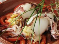 Tintenfischtuben mit Fischfüllung auf Tomatenscheiben