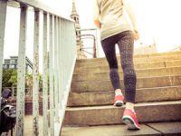 Gut trainierte Frau springt eine Treppe hinauf