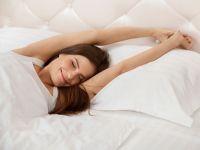 Junge Frau streckt sich nach dem Aufwachen im Bett