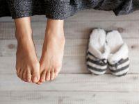 Frau streckt ihre nackten Füße aus dem Bett