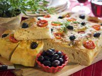Toskanischer Brotfladen (Focaccia) mit Tomaten und Oliven