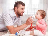 Vater füttert Baby