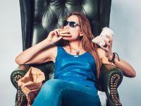 Frau sitzt mit Sonnenbrille auf einem Sessel und isst einen Burger