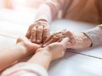 Eine junge Frau ergreift die Hände einer alten Frau