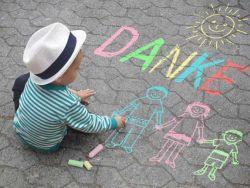Junge malt mit bunter Kreide danke und eine Familie auf den Asphalt