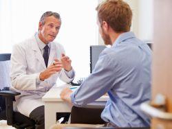 Mann sitzt im Sprechzimmer eines Arztes
