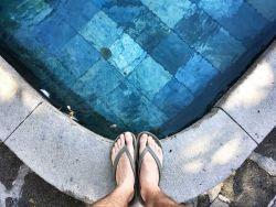 Männliche Füße in Flip Flops am Rand eines schönen Pools