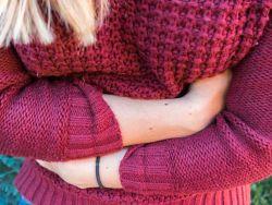 Morbus Crohn: Junge Frau hält sich den Bauch