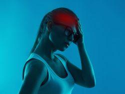 Frau fasst sich an den schmerzenden Kopf