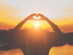Herz-Form aus Händen in der Sonne