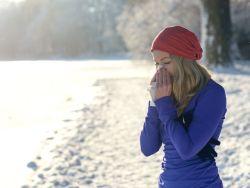 Junge Frau in sportlicher Kleidung im Schnee putzt sich die Nase