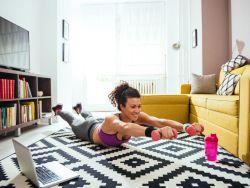 Attraktive sportliche Frau macht Hantelübungen auf ihrem Wohnzimmerteppich