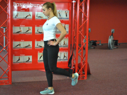 Frau im Fitnessstudio macht Beinübungen