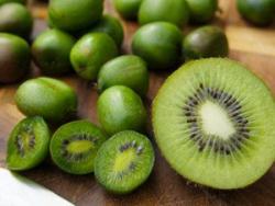 Angeschnittene Kiwibeeren neben einer normalen Kiwi