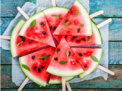 Wassermelonen-Dreiecke mit Eisstiel auf einem hübschen Brett drapiert