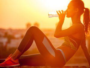 Frau trinkt vor Sonnenuntergang