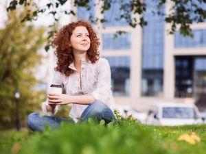 Rothaarige Frau sitzt mit To-Go-Kaffeebecher im Park, im Hintergrund ein Bürogebäude