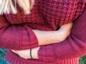 Junge Frau hält sich den schmerzenden Bauch