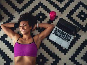 Frau in Sport-outfit liegt auf dem Teppich des Wohnzimmers und lächelt